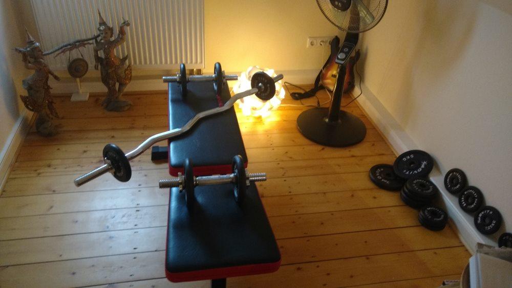 Fitnesstraining mit Hanteln und Hantelbank im Wohnzimmer
